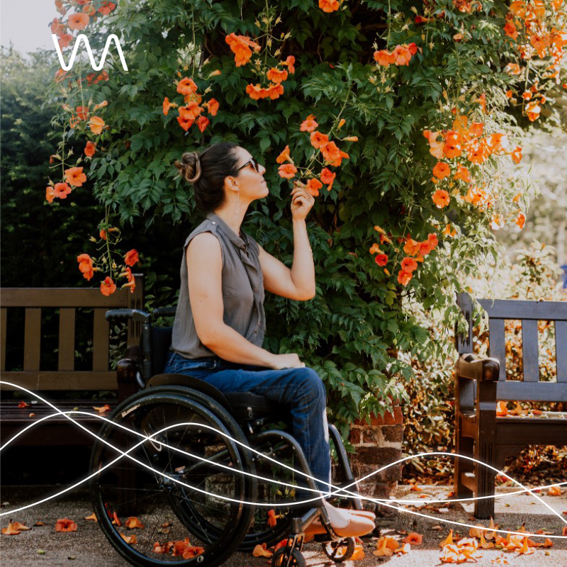 A woman sits in a wheelchair in a park. She is smelling a wall of orange flowers on green vines. She is wearing blue jeans and a brown top.